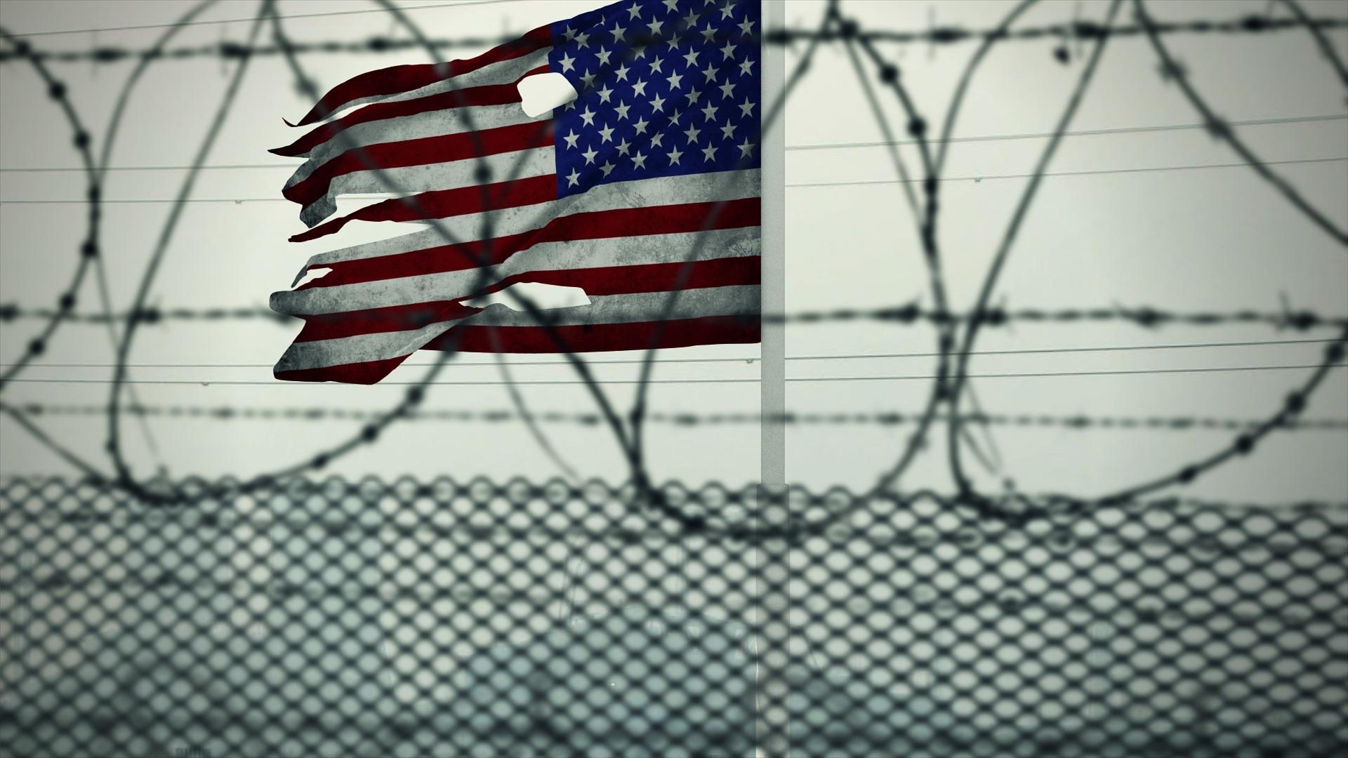 American flag behind jail fence