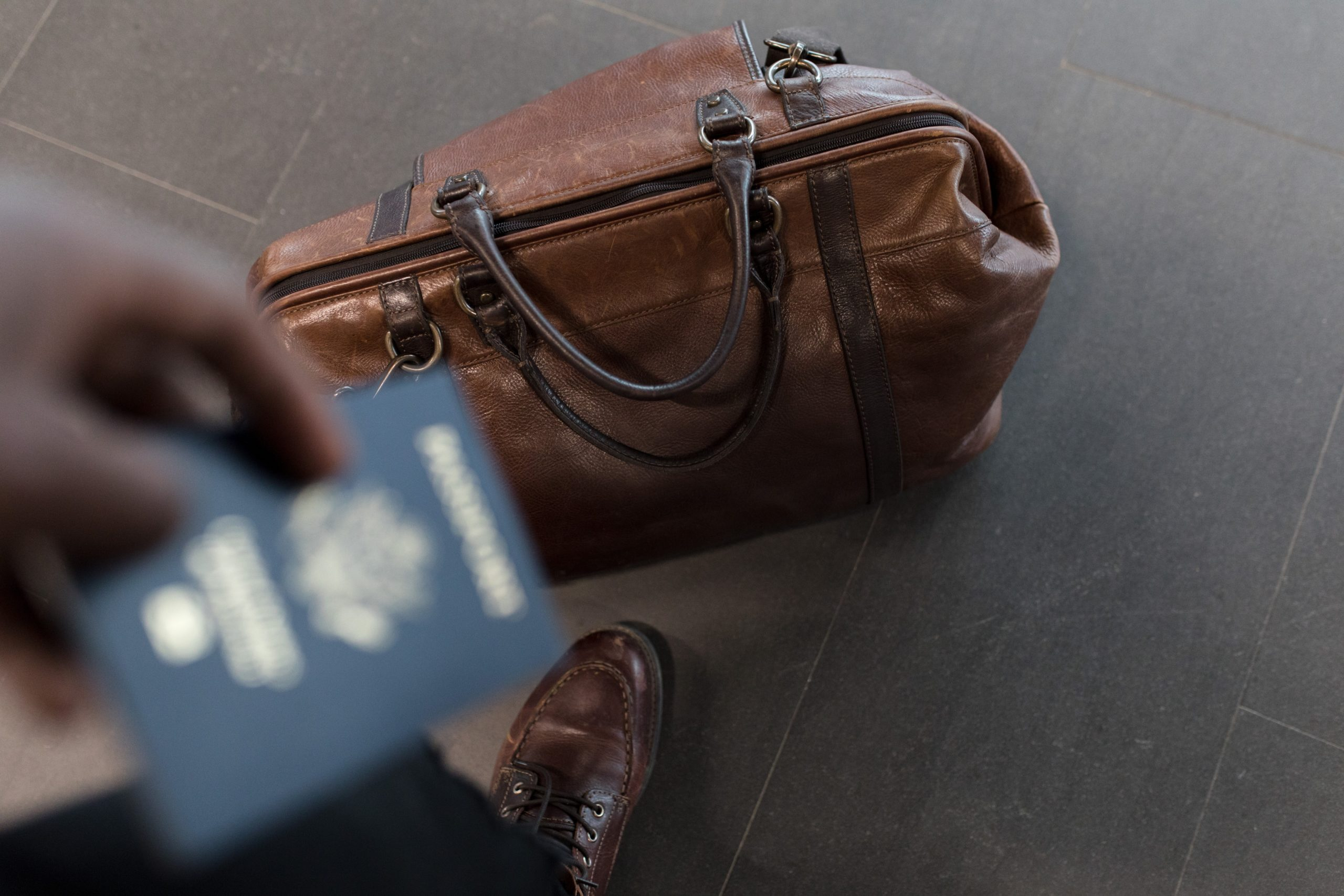 travel bag and person holding passport